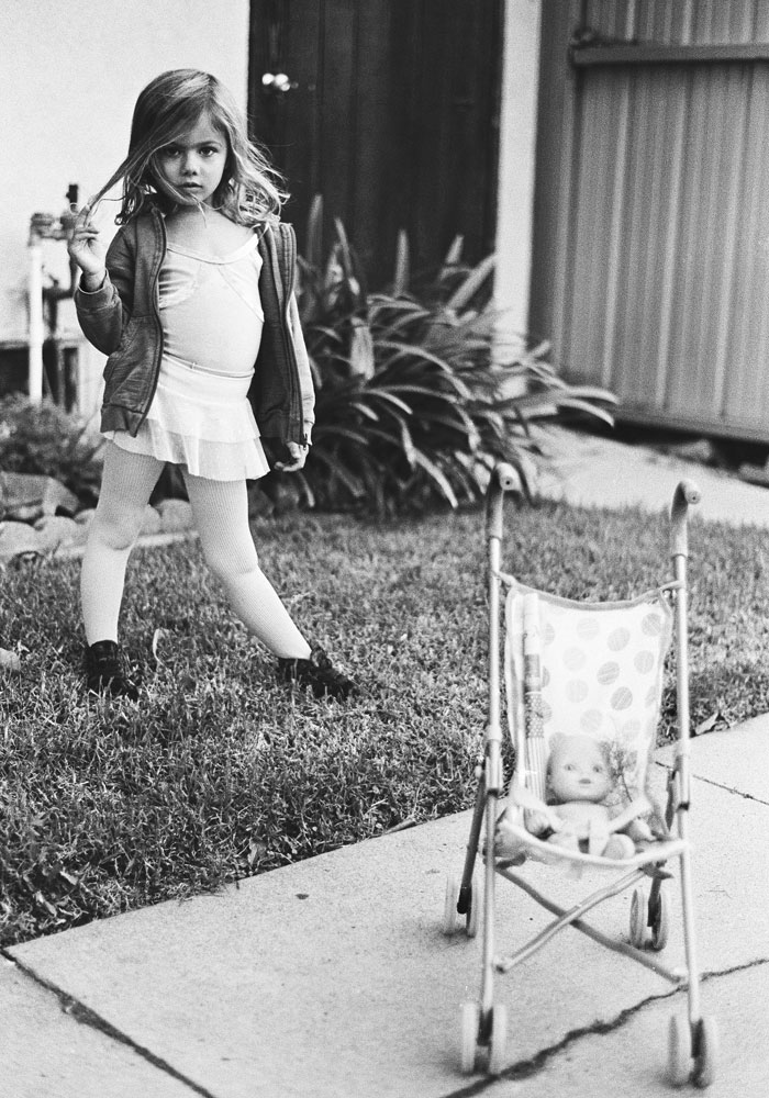 A young girl standing in her front yard, wearing a ballerina outfit and sweatshirt. Her doll and carriage sit on the sidewalk in front of her.
