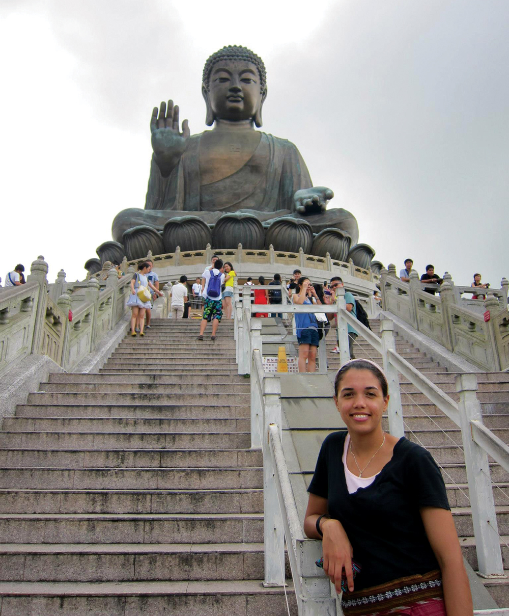 Amber Moore standing at the bottom of the steps below a giant statue in Hong Kong