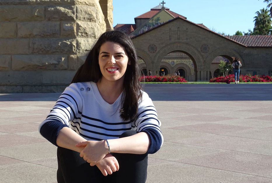 Abdullah smiling and sitting on the steps of the Main Quad of Stanford with Stanford Memorial Church in the background.