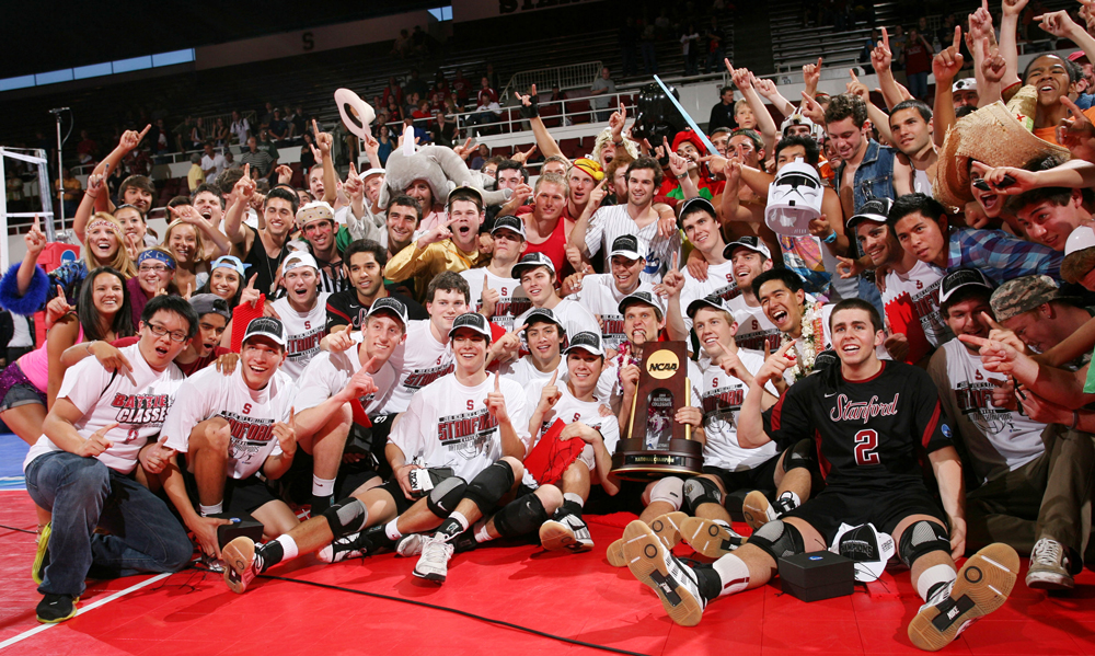 Stanford men's volleyball team and others sitting on court with the NCAA trophy after winning NCAA championship