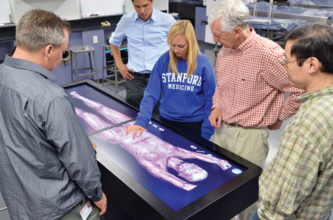 A student stands at an electronic dissection table, moving her hand to inspect portions of the body. Several faculty members look on.