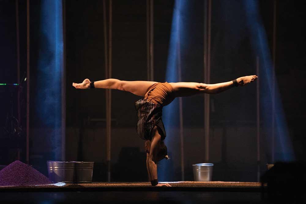 Acrobatic performer doing a handstand split.