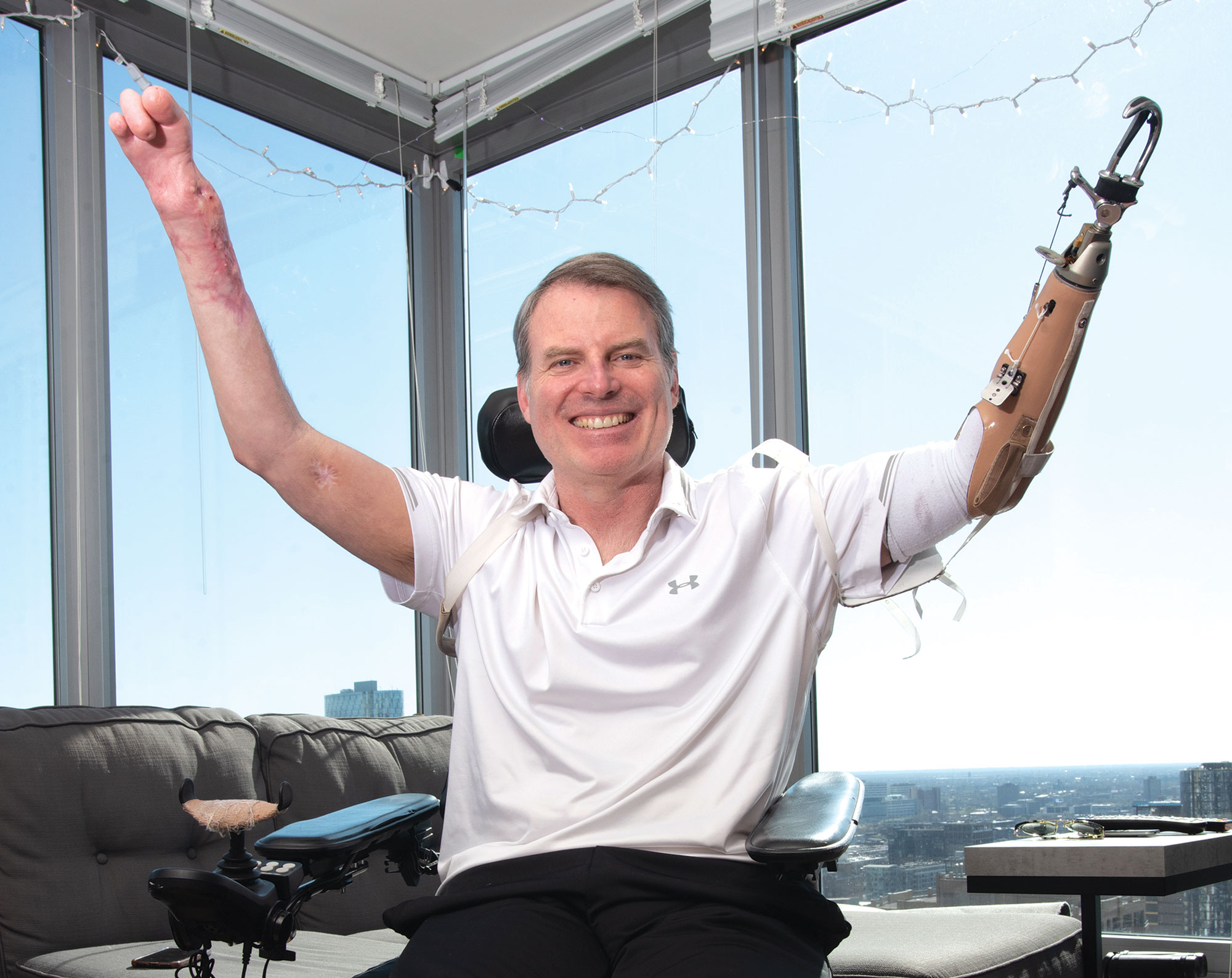 Marty Hartigan triumphantly raising his hands over his head in front of large window