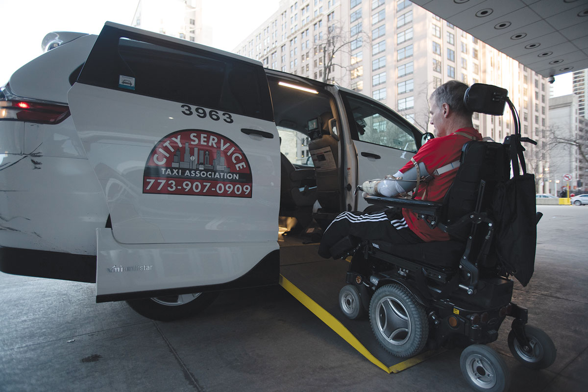 Marty Hartigan driving electric wheelchair inside a taxi