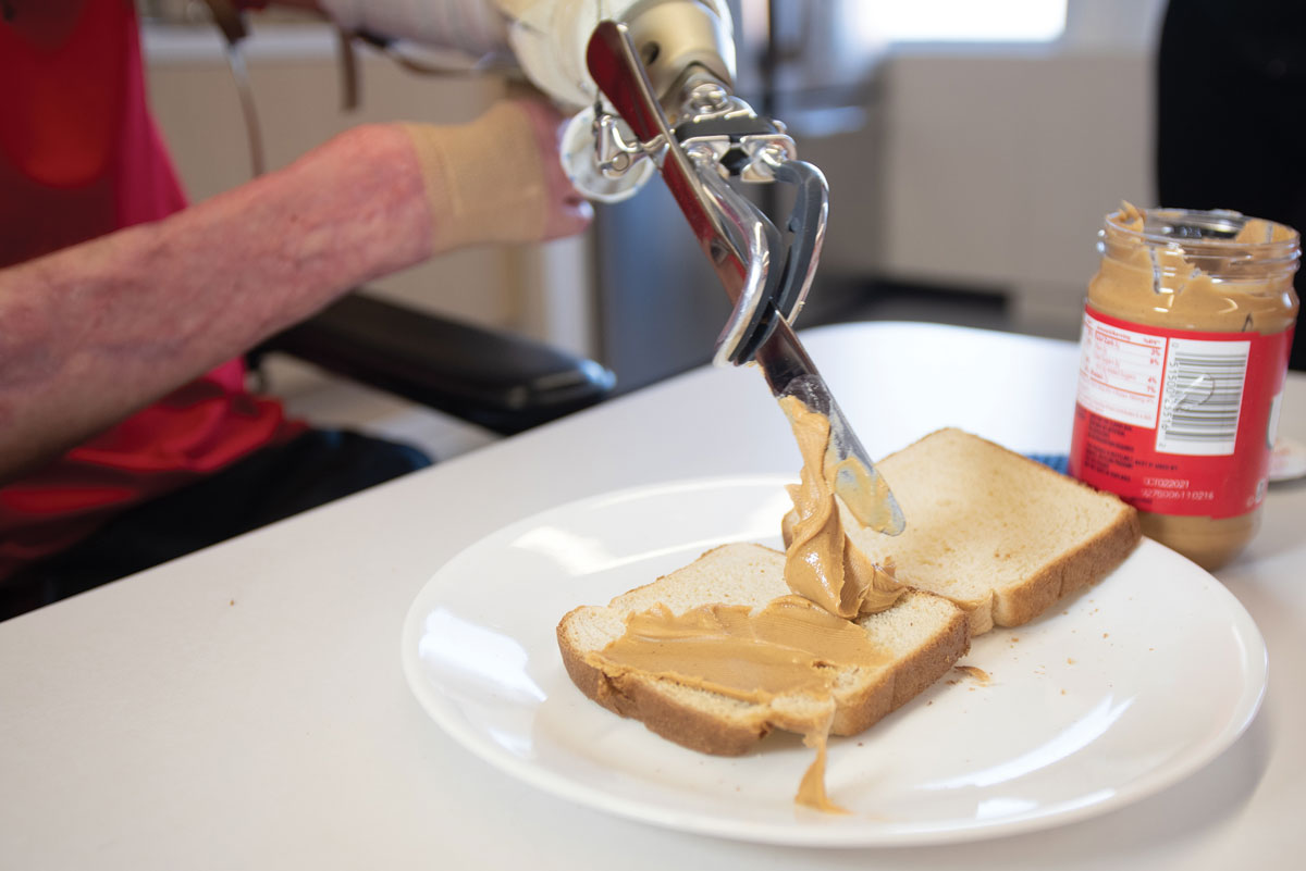 Marty Hartigan holding a knife, spreading peanut butter on bread