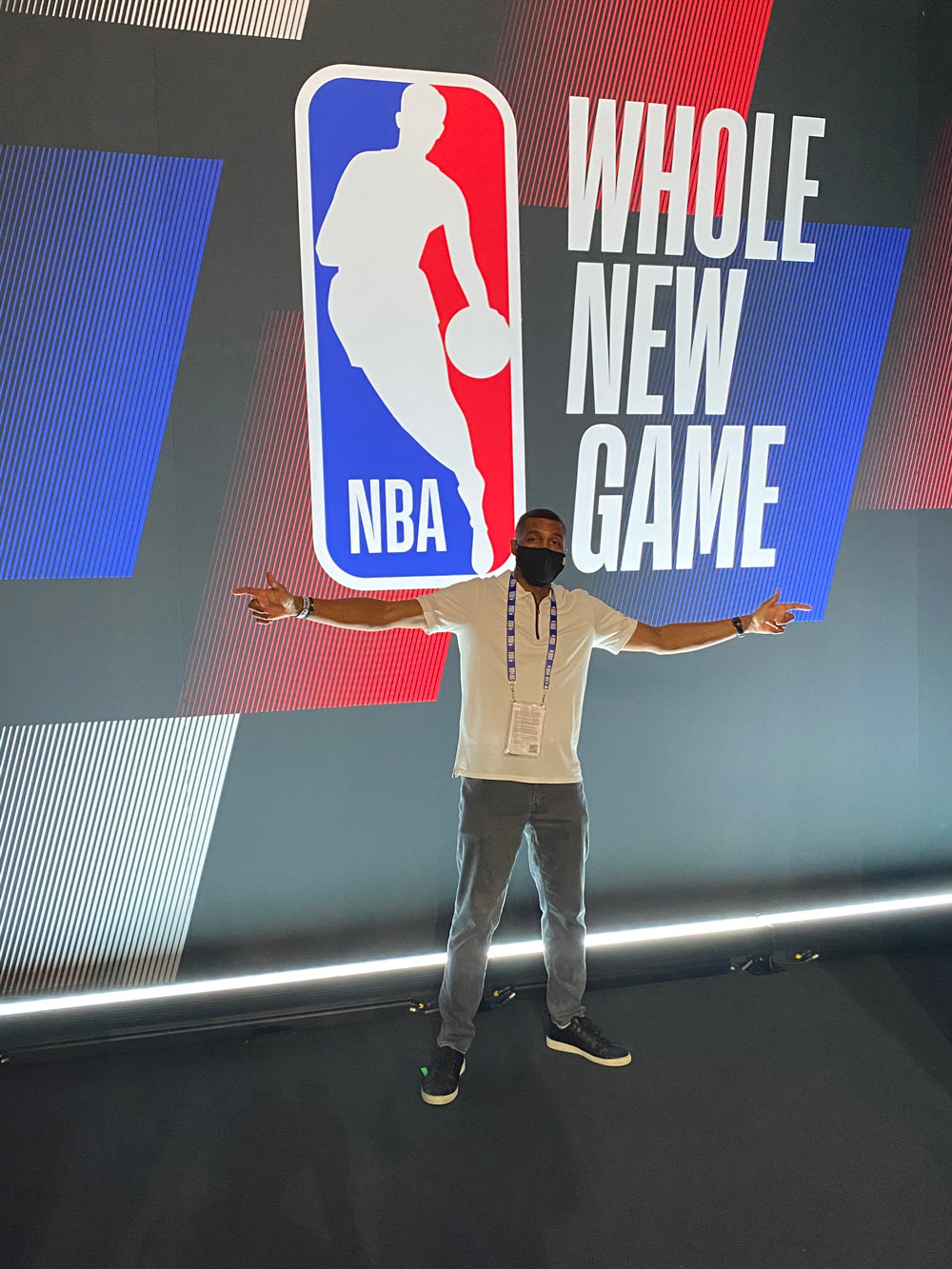 Leroy Sims wearing a mask in front of NBA sign inside the NBA bubble.