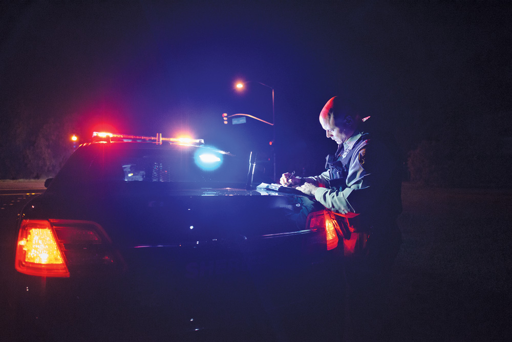 Deputy Perkins writing a ticket outside his vehicle