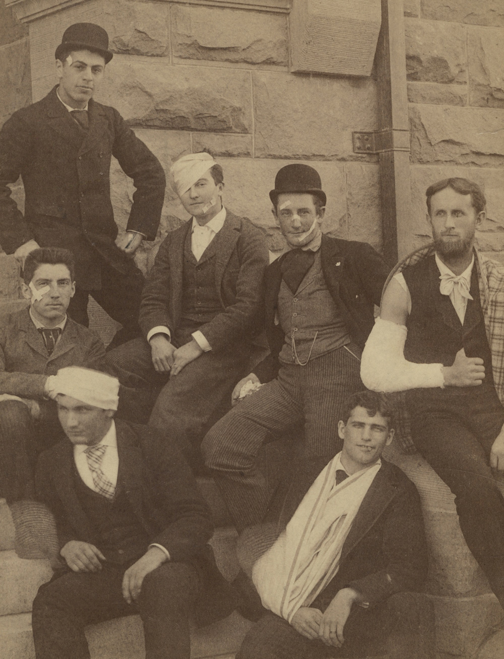 A group of wounded men sitting on the stairs of what appears to be main quad after a brawl.
