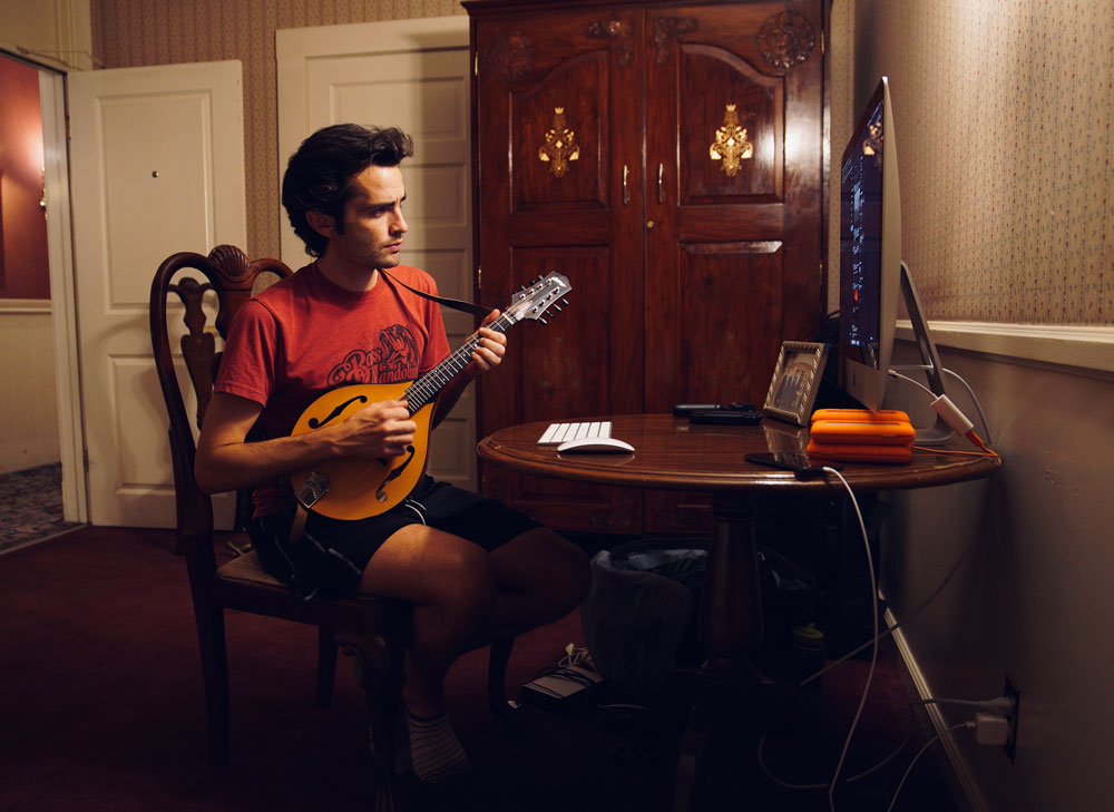 Austin Meyer sitting at a table playing a mandolin