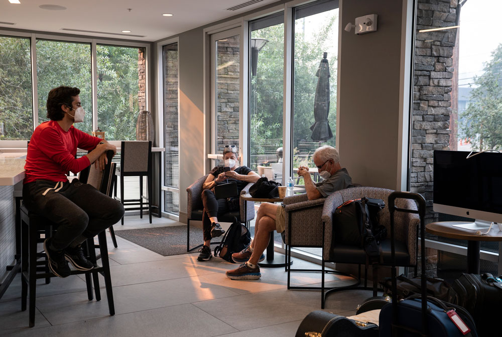 Austin Meyer and his parents wearing masks and sitting in a hotel lobby