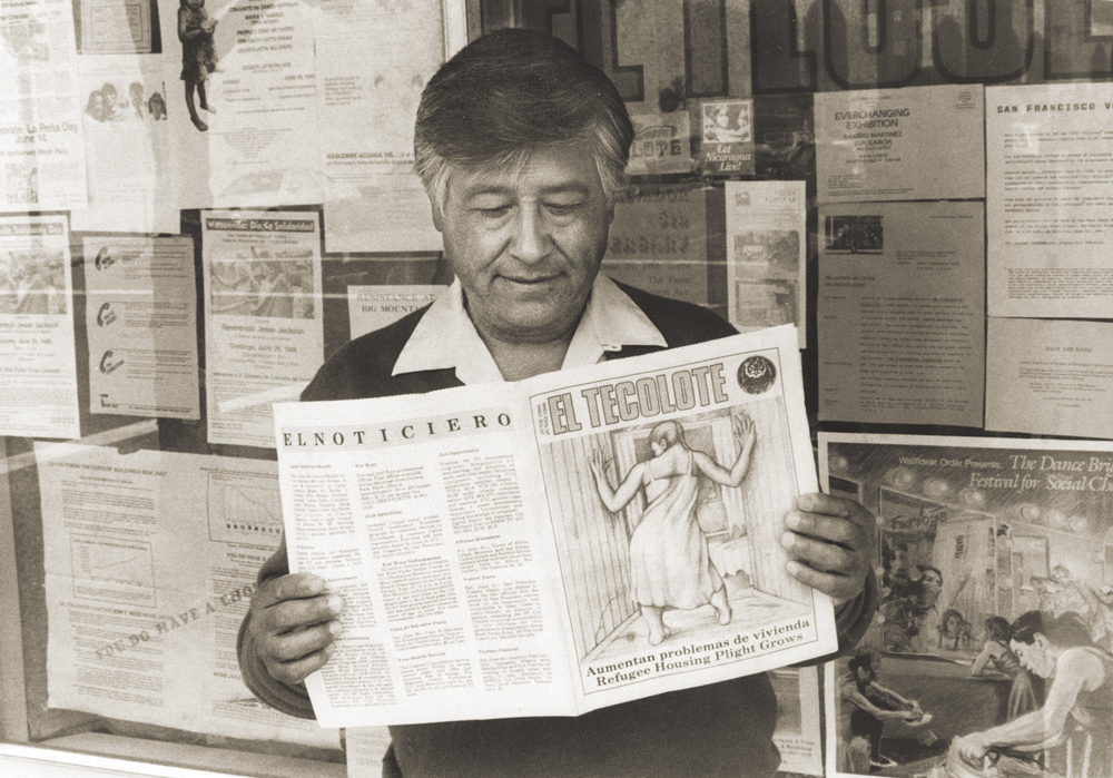A man reading El Tecolote outside a storefront window.
