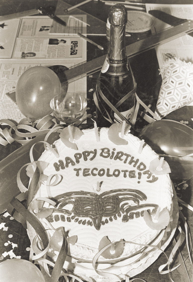 "A cake that says ""happy birthday Tecolote"" and a bottle of champagne on a table."