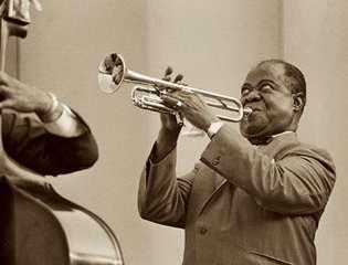 Louis Armstrong blows into a trumpet with vigor.