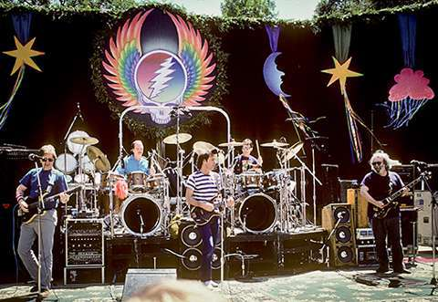A photo of the grateful dead playing on a decorated stage.