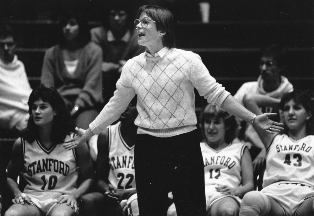VanDerveer standing in front of players on the bench coaching a game