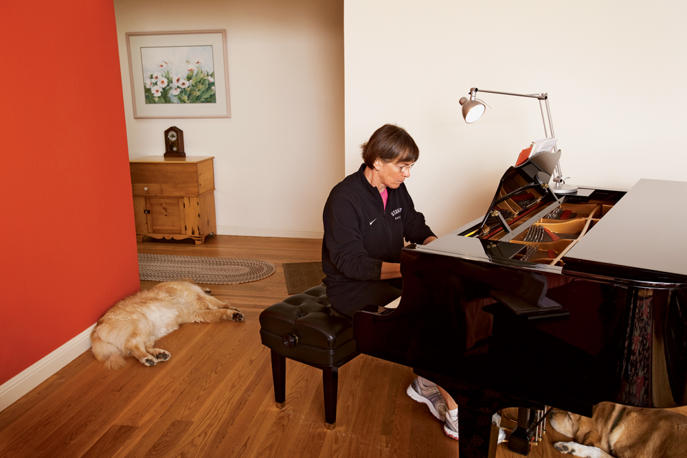 VanDerveer playing her piano with her dogs asleep on the floor