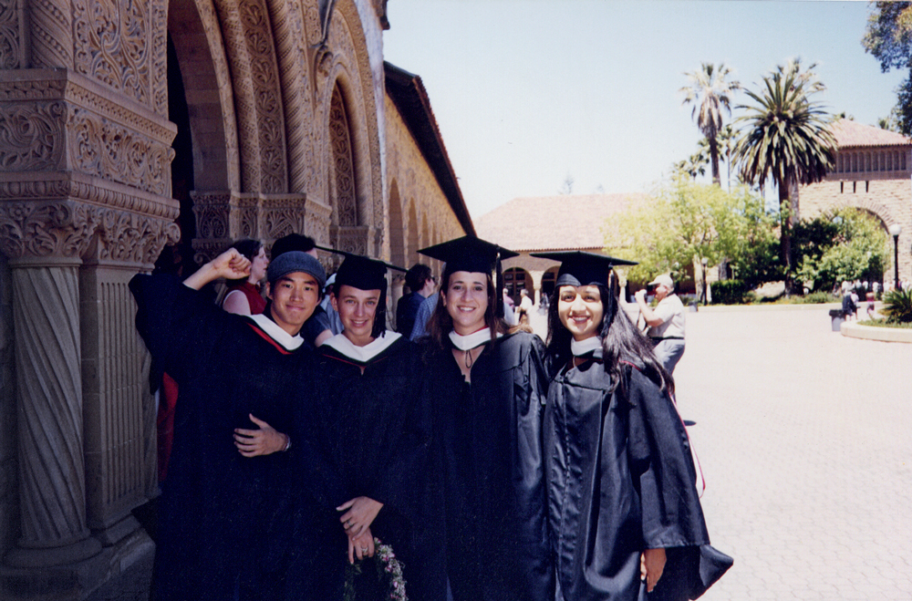 Lee and three others in cap and gown in Stanford's Main Quad.