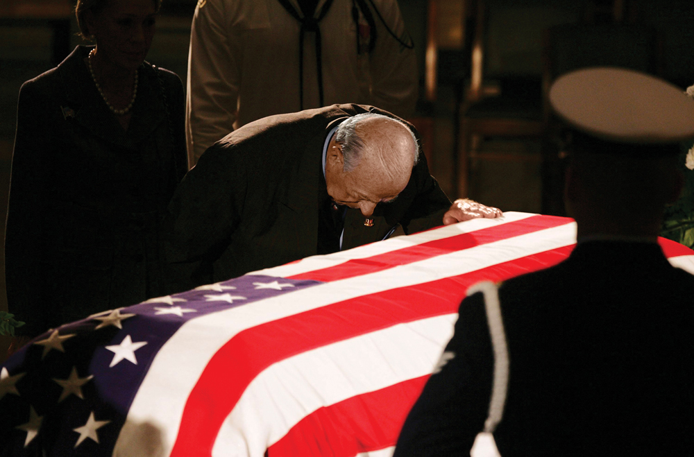 Shultz kneels, head down, with his hand on Reagan's casket.