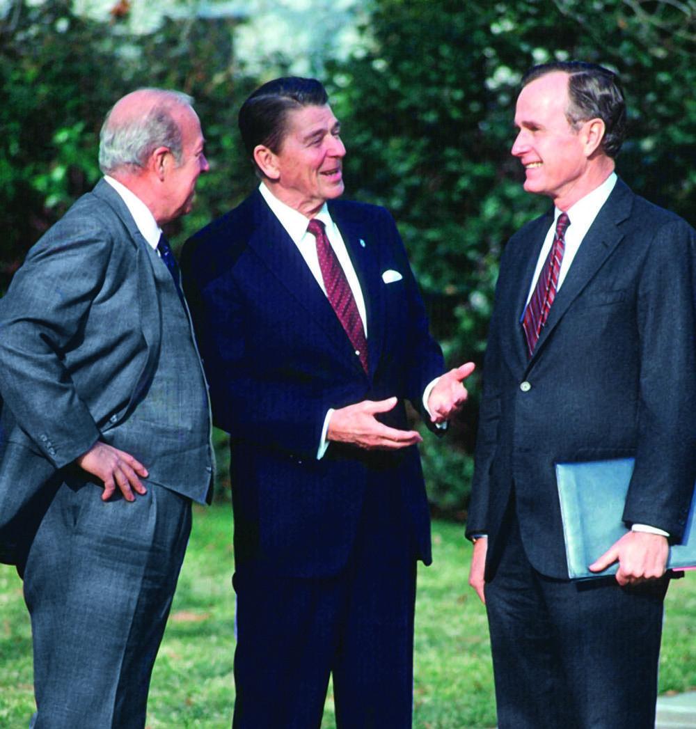 Shultz, Reagan and George H.W. Bush talk outdoors.
