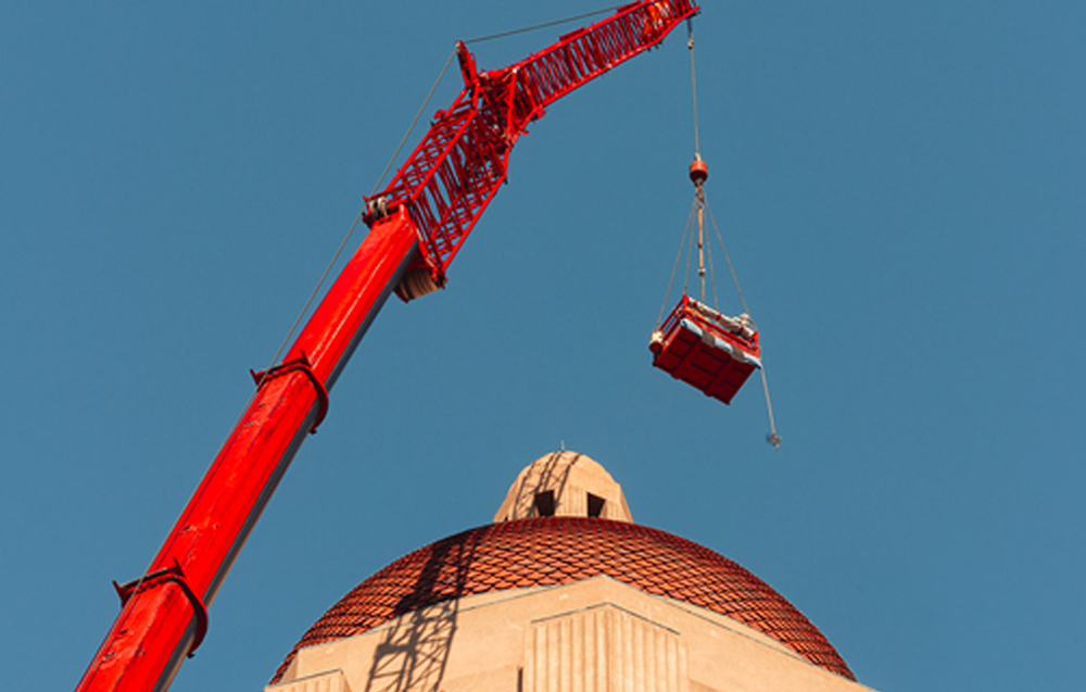 Crane replacing top of Hoover Tower