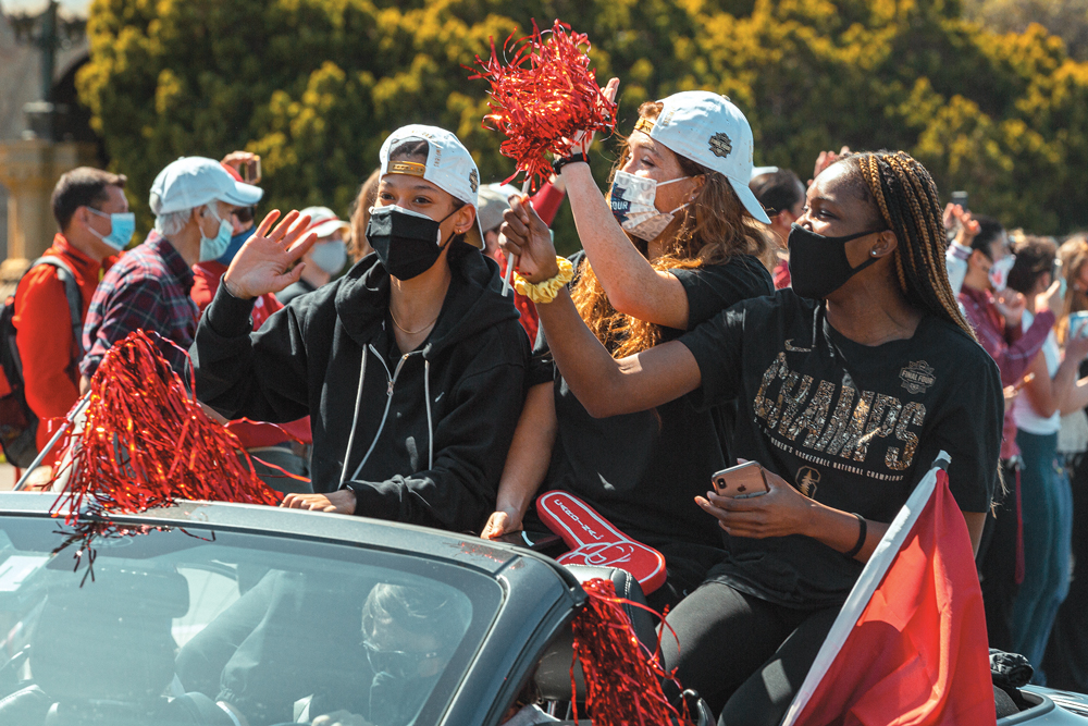 Women's basketball player in masks riding in convertible