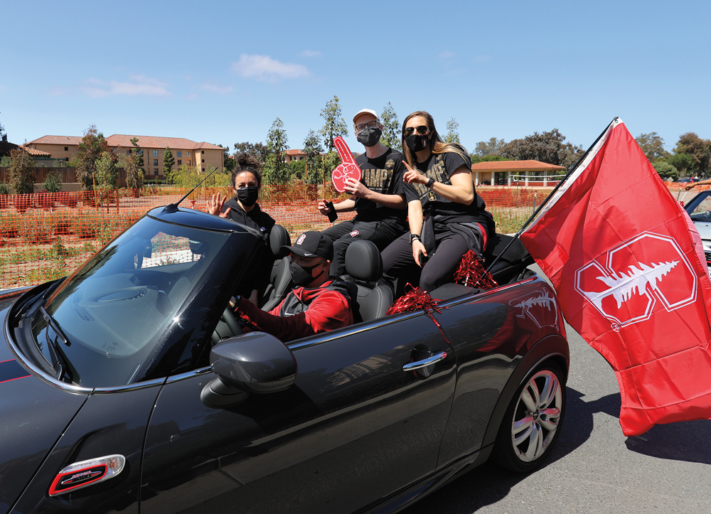 People in masks riding in convertible with Stanford flag