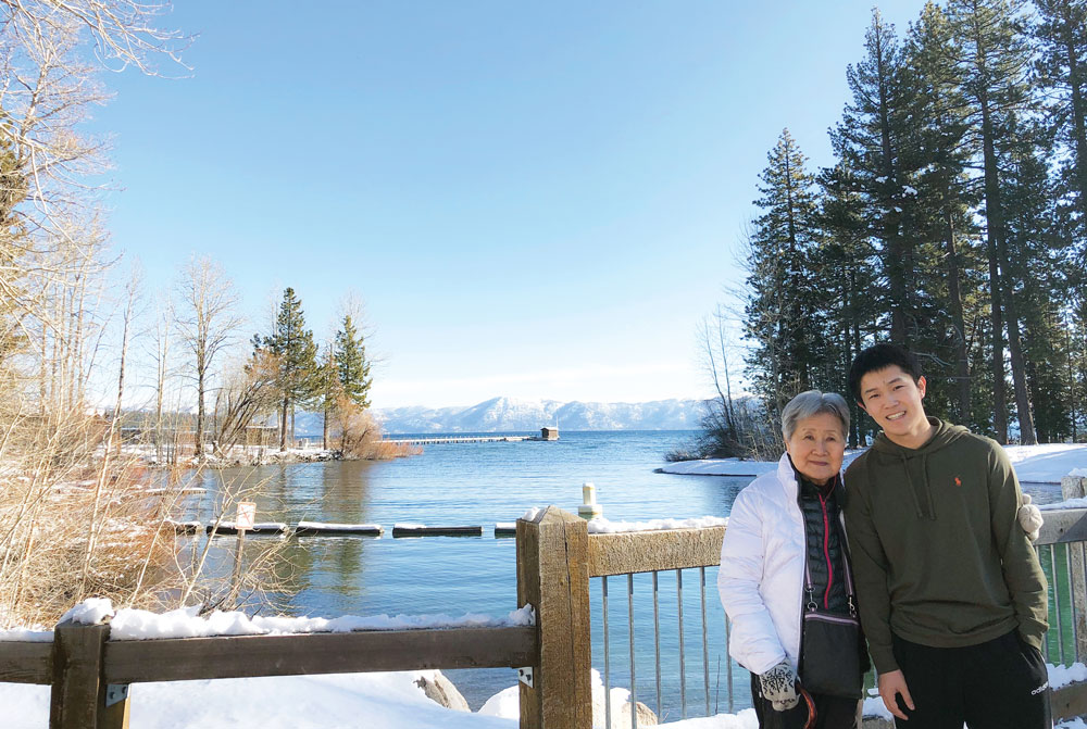 Andrew Tan with his grandmother at a lake in the winter.