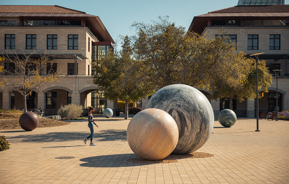 Masked student walking by marble sphere sculptures