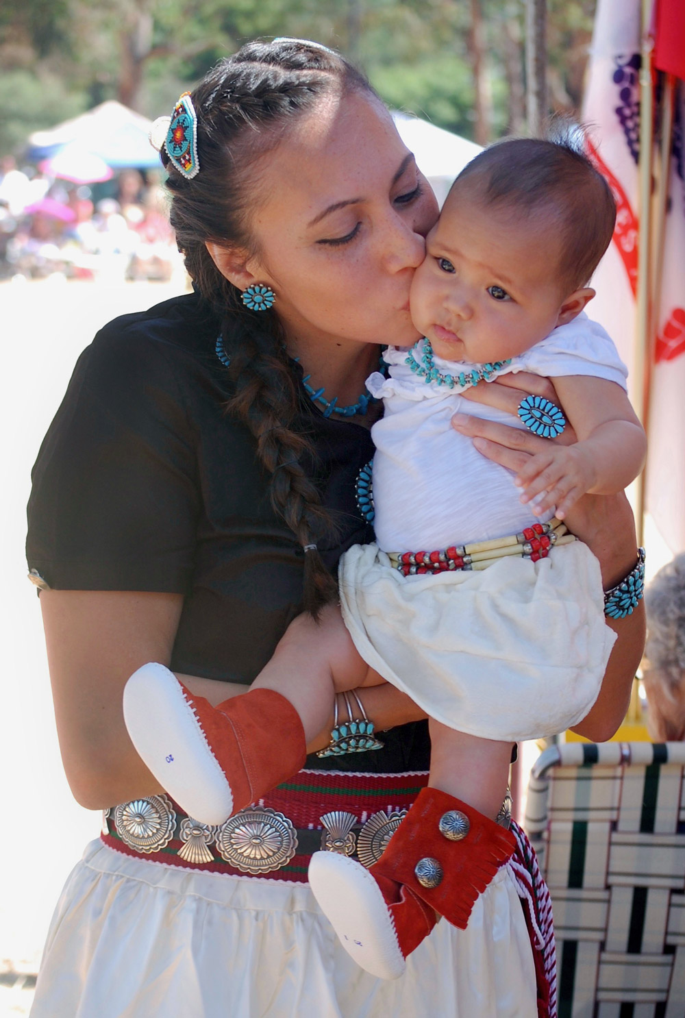 Ginger Sykes Torres holding and kissing her child.