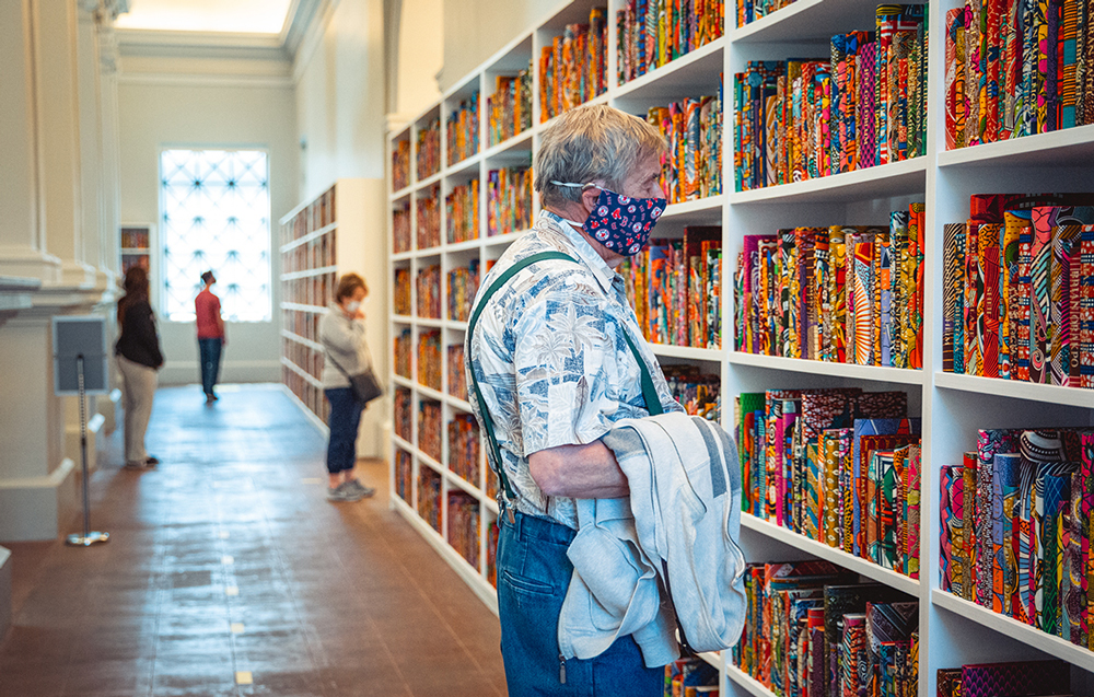 Man in a mask looking at shelves of colorful books.