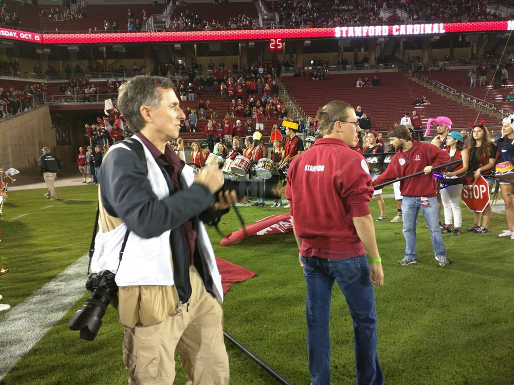Robby Beyers on the sidelines of the football field holding his camera
