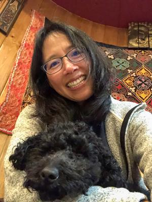 Grace Chin Hartman snuggling a black dog