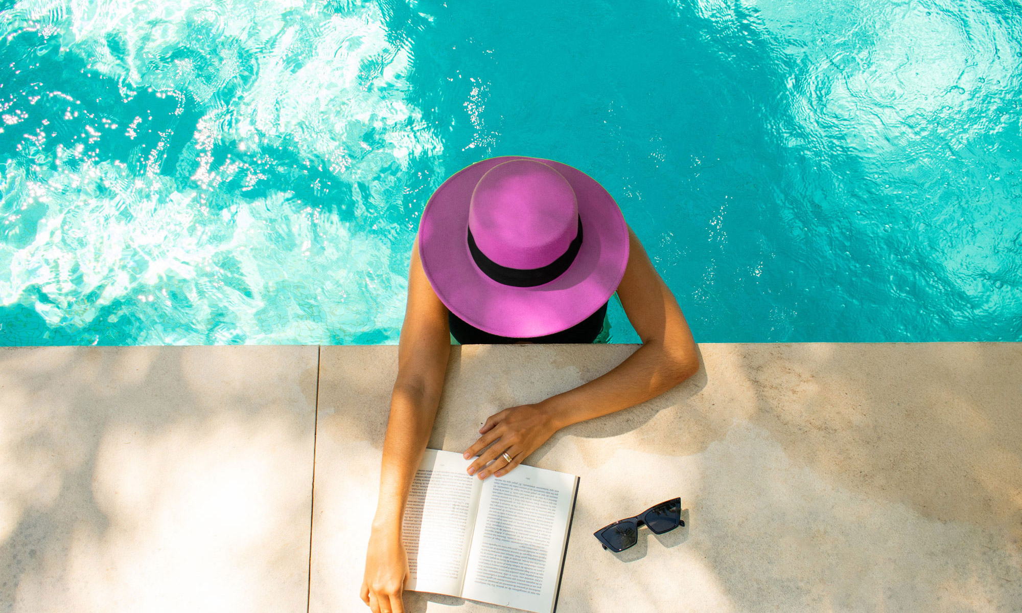 Woman wearing hat in pool reading a book