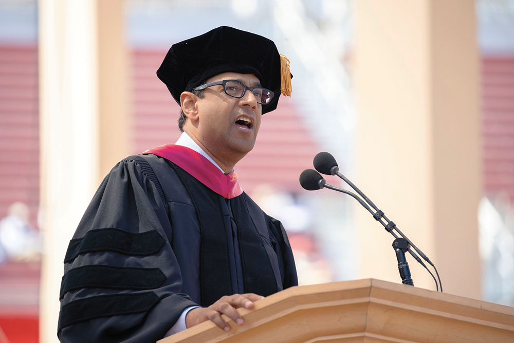 Atul Gawande in cap and gown speaking at the podium.