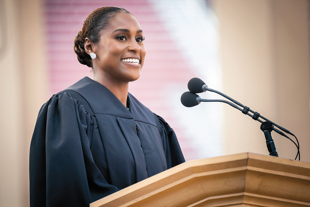 Issa Rae at the podium in commencement gown.