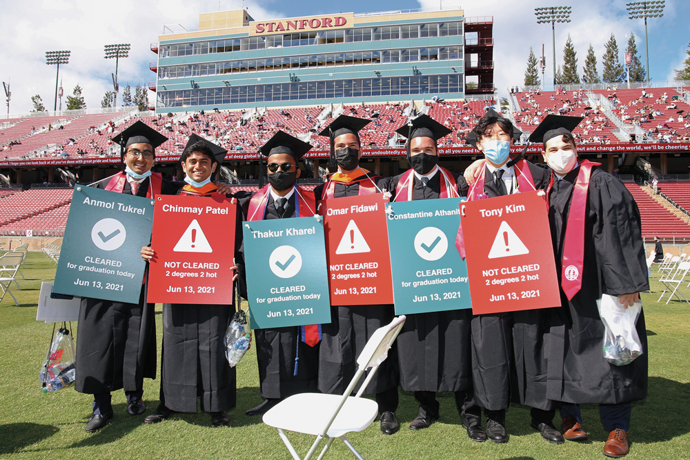 """Graduates at Wacky Walk wearing """"health check—cleared for graduation"""" signs."""