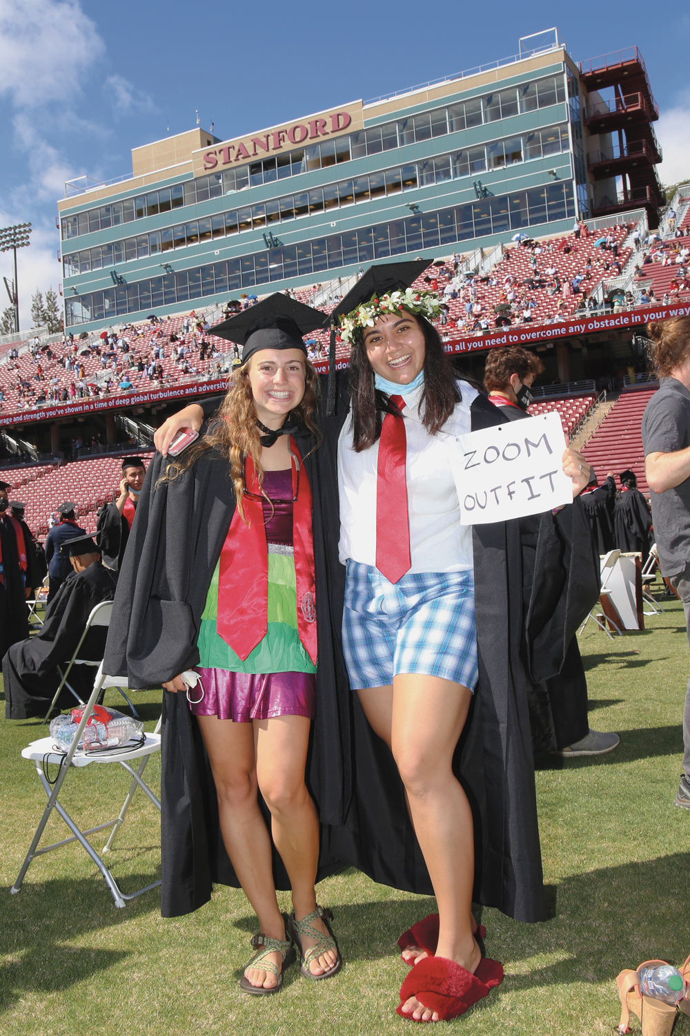 """Two female graduates with gowns open, revealing shirts and ties on top, and casual shorts on the bottom; one is holding a sign that says """"Zoom outfit."""""""