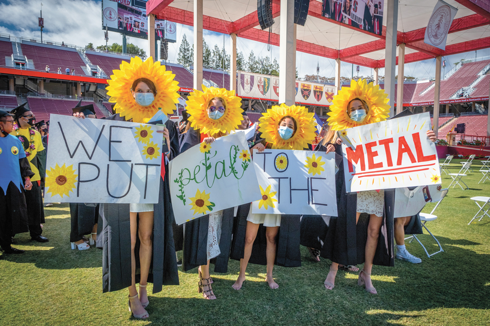 """Graduates dressed as flowers with signs that read """"We put petal to the metal."""""""