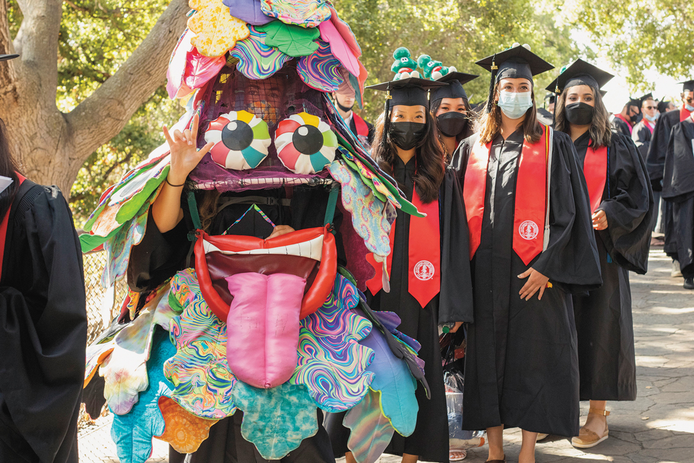 The Stanford Tree followed by graduates in cap and gown wearing masks.