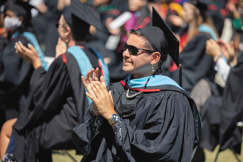 Advanced-degree graduate sitting cap and gown, applauding..