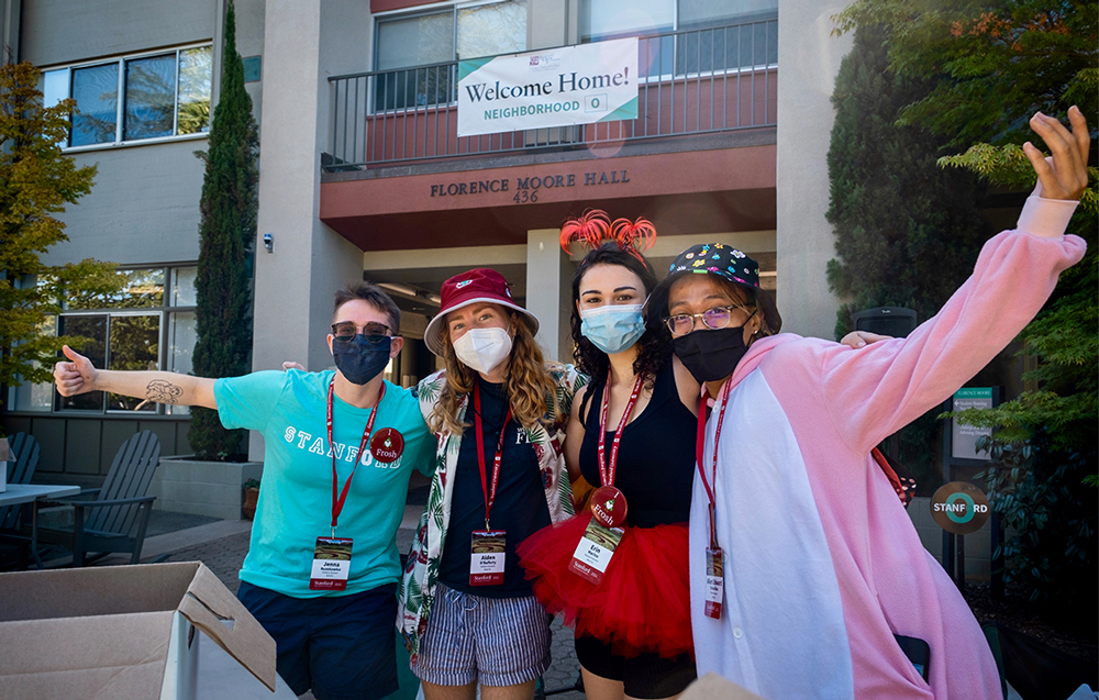 Happy students in masks outside Florence Moore Hall
