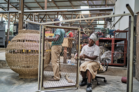 Two people are busy in a large workshop facility. One sits on a chair and fidgets with part of an iron fence. Another appears to be weaving a large basket.