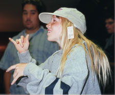 A younger Kolb is seen at summer camp. She is wearing a large hoodie and a baseball cap. She signs with her hands.