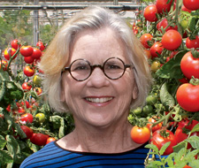 Ann Powell standing in a greenhouse full of tomato vines.